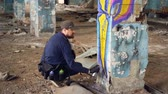 vandal : Graffiti artist bearded guy is painting on pillar in abandoned building with aerosol paint spray. Empty industrial building with dirty walls and floor is in background.