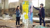 grafiti : Slow motion of skilled graffiti artists bearded guy and attractive young woman working together in abandoned warehouse decorating damaged column with abstract image.
