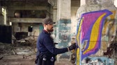 vandal : Young man professional graffiti painter is working inside abandoned building, he is painting with spray aerosol paint on damaged column. Modern art and creativity concept.