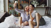 память : Modern married couple is taking selfie in bedroom gesturing posing and kissing while sitting on bed together. Modern technology and people concept.