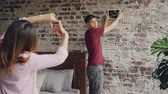 tehcir : Handsome guy is picking place on brick wall to hang modern picture while his girlfriend is making frame with her fingers and gesturing approving his decision with thumb-up. Stok Video