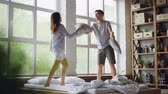 pigiama : Slow motion of excited young people having pillow fight on double bed, they are having fun jumping and laughing. Happy couple, relationship and entertainment concept. Filmati Stock
