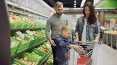 owoc : Young family with child is shopping for food in supermarket, parents are choosing fruit and boy is putting them in shopping cart. Grocery store and family life concept.