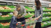 cheiro : Father, mother and child are choosing pineapple in grocery store touching and smelling it showing thumbs-up. Shelves with delicious fruit and shopping trolley are visible. Vídeos