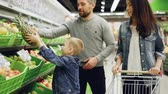 owoc : Happy young family mother, father and child are buying fruit in supermarket putting pineapple in shopping cart, talking and smiling. Food store and people concept. Wideo