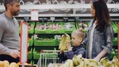cheiro : Mom, dad and cute boy are choosing fruit in food store, child is smelling bananas and giving them to his father, man is putting fruit in shopping trolley. Vídeos