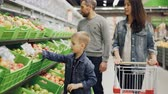 owoc : Young family mom, dad and little boy are choosing fruit in supermarket touching and smelling them and putting in trolley. Shopping for food and people concept.