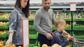 diário : Young family with cheerful child is walking through food store with shopping cart and choosing fruit smelling and touching them. Buying food and people concept.