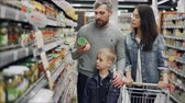 conserva : Married couple with cute little son are shopping for food, they are taking glass can from shelf and checking ingredients and expiry date and talking.