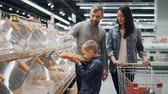pastelaria : Young family is choosing bread in bakery department in supermarket, little boy is taking loaf from plastic container and smelling it then putting in trolley.