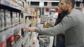 kupující : Young woman is choosing tea in food store, her husband and son are helping her looking at products and talking. Buying food and drinks in supermarket concept. Dostupné videozáznamy