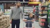 cart : Dolly shot of young family father and son walking through food store with trolley looking around and talking. Shopping together, happy people and supermarket concept. Stock Footage