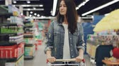 corredor : Attractive woman is driving shopping trolley through food department in supermarket and looking around. Pretty girls, everyday life and buying products concept. Vídeos