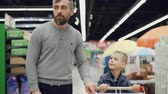 cart : Cheerful man is shopping with his joyful child, they are walking with shopping trolley in supermarket looking around, pointing at goods, talking and laughing. Stock Footage