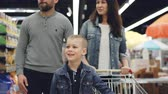 diariamente : Cheerful young family mom, dad and little boy are walking together in hypermarket with shopping trolley looking around, pointing at food and talking. Vídeos