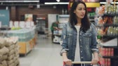 corredor : Pretty young lady is walking through aisle in supermarket with shopping cart looking at shelves with products, employees in uniform are working in background.