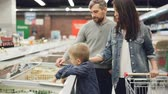 refrigerator : Little boy is opening freezer and taking pack of frozen vegetables then giving it to his daddy while shopping in supermarket with his family. People and shop concept. Stock Footage