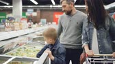 bag check : Modern family is buying precooked frozen food in supermarket, boy is opening refrigerator and taking bag, his parents are checking expiry date and ingredients contents. Stock Footage