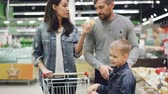 cheiro : Mother, father and son happy family are choosing cheese in dairy department of supermarket, they are taking pieces from fridge and smelling them, then putting in cart.