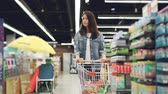 go cart : Dolly shot of pretty young lady with shopping cart walking along rows of shelves with products and looking around with smile. Shopping for food and people concept.