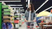 corredor : Young pertty brunette is walking in hypermarket and pushing shopping trolley going to buy food and looking around at shelves with products. People and shops concept. Vídeos