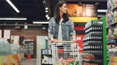 corredor : Pretty lady in casual clothes is walking in grocery store steering shopping trolley with food inside it and looking around at shelves with products. Women and shops concept. Vídeos
