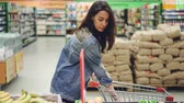 kupující : Pretty woman happy customer is buying fruit in supermarket choosing bananas and apples and putting them in shopping cart. Healthy lifestyle and shops concept.