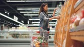 diário : Smiling girl is buying fresh bread in supermarket smelling it then putting in cart with other products. Shopping for food, cheerful people and happy customers concept.