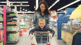 empurrando : Joyful loving mother is having fun in supermarket with her cute little son, she is running with shopping cart with small boy standing on it, people are laughing. Stock Footage