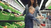 cart : Cute blond boy is shopping with his mother buying fruit, he is taking apple from plastic box and putting it in trolley, his mom is smiling and talking to her son.