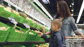 departamento : Adorable little boy is choosing apples in fruit and vegetables department in grocery store, his attractive mother is standing beside him and talking to her son. Vídeos