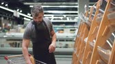 pastelaria : Busy salesman is putting bread on shelves in bakery department in food store, bearded guy is wearing apron. Selling products, profession and trade concept.