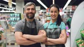 supermarket : Portrait of two supermarket employees attractive people in aprons standing inside shop, smiling and looking at camera. Shelves with food and drinks are visible.