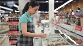 refrigerator : Attractive female saleswoman in apron is busy putting bags with precooked food in freezer. Bright products on shelves are visible, customers are walking around. Stock Footage