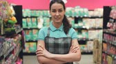 продавщица : Portrait of attractive young saleswoman in apron standing in supermarket with her hands crossed, looking at camera and smiling. Trade business and people concept.