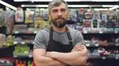departamento : Portrait of handsome bearded guy experienced salesman in apron standing in toy department in supermarket, looking at camera and smiling. Shop and people concept.
