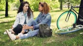 рюкзак : African American girl is chatting with her Caucasian friend sitting on grass in park, friends are talking and smiling. Modern bicycles and knapsacks are visible.