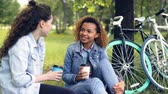 takeout : Young African American woman is chatting with her Caucasian friend and drinking takeaway coffee relaxing in beautiful park after riding bikes on sunny summer day. Stock Footage