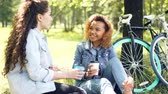 takeout : Two female cyclists are having rest drinking coffee sitting on lawn in park and chatting after riding bikes. Active lifestyle, modern young people and leisure concept.