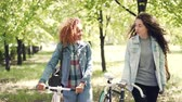 ciclista : Dolly shot of cheerful girls friends walking in park with bikes relaxing after riding bicycles and socializing. Multiethnic friendship, hobby and active lifestyle concept. Vídeos