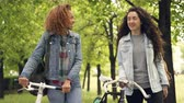 drby : Happy friends beautiful women are walking in park holding bicycles and talking cheerfully, beautiful nature trees and grass in background. Friendship and hobby concept.