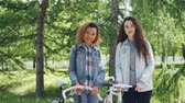 mischwald : Portrait of happy young women Caucasian and African American standing together in nice green park, holding bikes, looking at camera and smiling. People and nature concept. Stock Footage