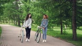 estrangeiro : Dolly shot of beautiful young girls African American and Caucasian walking in park along path with bikes and talking. Green trees and lawns are visible.