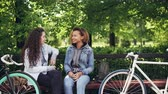 многонациональная : Cheerful female friends are talking discussing news sitting on bench in town park with bikes and bags visible. People are walking in background along paths between trees.