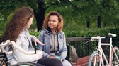 сиденья : Young women tourists are having conversation sitting on bench in park and holding takeaway coffee with bikes standing nearby. Tourism, people and communication concept.