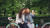 takeout : Female friends are taking selfie with smartphone sitting on bench in park holding coffee, young women are posing with silly faces having fun enjoying free time.