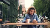 wi fi : Happy African American girl is using smartphone touching screen and smiling while sitting in outdoor cafe in park. Knapsack and bicycle are visible.