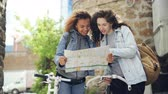estrangeiro : Two tourists are looking at map standing in the street holding bicycles and talking. Attractive young women and casual clothes with backpacks are laughing and looking around. Vídeos