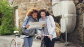 ciclista : Excited young women bike travellers are looking at map and laughing looking around while standing with bicycles in the street in foreign country. People and travelling concept. Archivo de Video