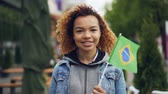 flaga : Slowmotion portrait of cheerful African American girl looking at camera and holding Brazilian flag standing in nice park in modern city. Tourism and people concept.